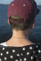 Close-up rear view of boy against lake