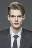 Portrait of confident young businessman over gray background