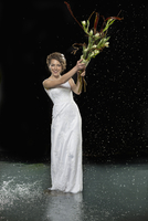 Full length portrait of smiling young bride holding bouquet while standing in water against black ba