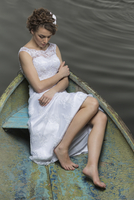 Full length of young bride sitting in boat on lake