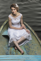High angle portrait of young bride sitting in boat on lake