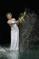 Excited young bride splashing water with bouquet against black background
