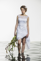 Portrait of young bride holding dress and wilted bouquet while standing in water against white backg