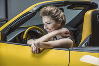 Happy woman looking away while sitting in convertible
