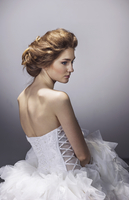 Sad young bride in wedding dress standing against gray background