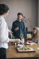 Young man with female friends talking while having breakfast at home