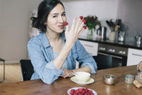 Portrait of happy young woman holding raspberries on fingers at home