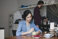 Young woman stirring coffee at kitchen table with man in background