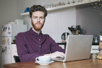 Portrait of confident young man using laptop at table in kitchen
