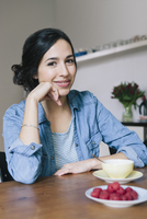 Portrait of happy young woman sitting at table in kitchen