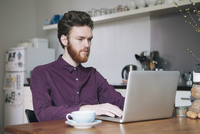Confident young man using laptop at table in kitchen