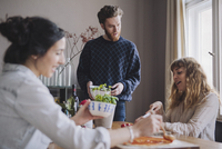 Young man with female friends making pizza at table