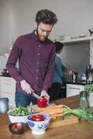 Young man chopping red bell pepper at kitchen table with woman in background