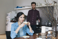 Portrait of young woman having coffee at kitchen table with man in background