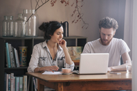 Young couple having discussion with laptop on table at home