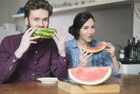 Portrait of happy young couple eating watermelon at kitchen table