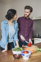 Young man chopping red bell pepper while looking at woman in kitchen
