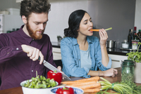 Young man chopping red bell pepper beside woman eating carrot at kitchen table