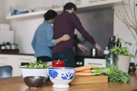 Vegetables on kitchen table with couple cooking in background