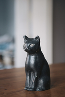 Bronze statuette of black cat on table