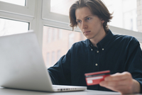 Young man holding credit card while using laptop at table