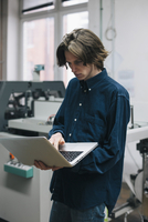 Young male technician using laptop in factory