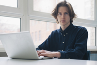 Portrait of confident young man using laptop at a desk
