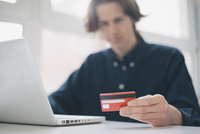 Young man holding credit card while using laptop at a desk