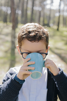 Close-up of boy drinking coffee in forest