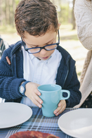 Boy holding coffee mug at table in forest