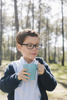 Boy holding coffee mug in forest
