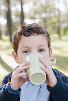 Close-up portrait of boy drinking coffee in forest