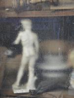Statue seen through wet glass window