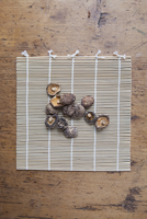 Directly above of dried white mushrooms on bamboo mat