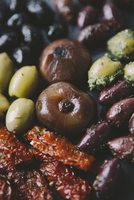 Close-up of various olives with onions and sun dried tomatoes