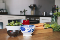 Vegetables and bowls on wooden table in kitchen