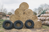 Stacked hay bales and tires on farm
