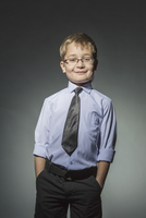 Portrait of well-dressed boy standing against gray background