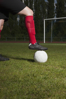 Low section of soccer player with foot on ball in front of goal post