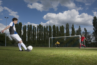 Full length of young soccer player kicking ball towards goal post