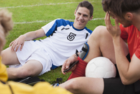 Young soccer players relaxing on field