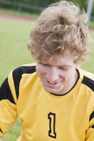 Happy young soccer player sitting on field
