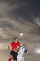 Male soccer players heading ball against sky