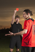 Referee showing red card to soccer player