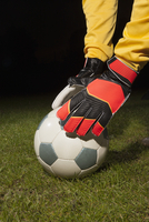 Cropped image of young male goalie placing soccer ball on field