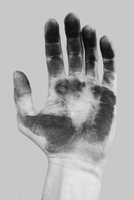 Close-up of dirty hand over gray background
