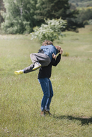Full length of playful mother carrying son on grassy field