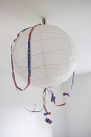 A paper lantern hanging from ceiling with a streamer around it