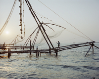 Mid distance view of man walking on commercial fishing net at sea during sunset