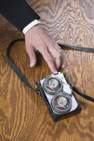 Cropped image of businessman using old-fashioned tape recorder on wooden table